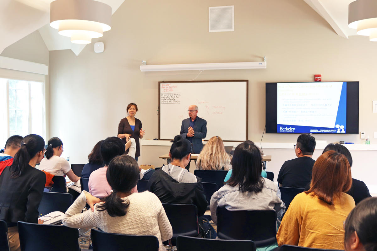 asian female counselor and white male counselor giving presentation to large group